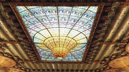 The Glow Worm looks like a droplet of water that is forever waiting to fall. This gorgeous glass construction dominates the ceiling. The droplet of the Glow Worm is like The Palau's own sun, surrounded by a choir of stained glass women that sing its praises.